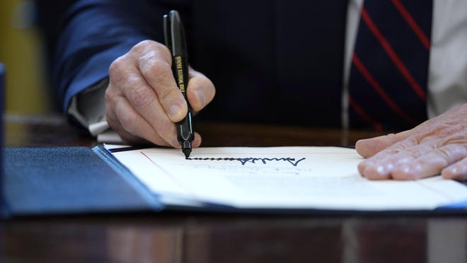 President Donald Trump signs the initial coronavirus stimulus relief package in March.