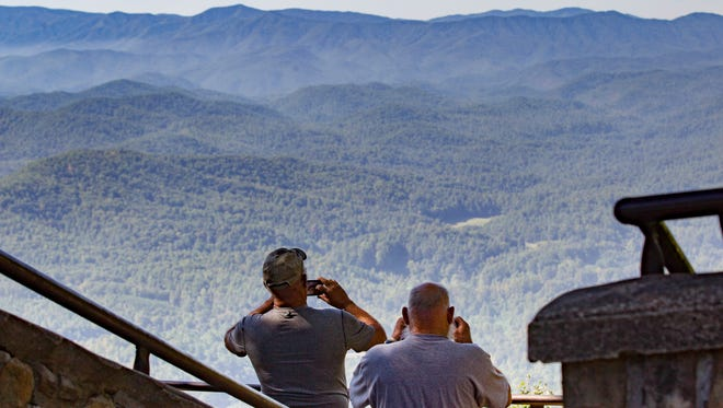In this Sept. 15, 2016, photo, visitors take pictures of the Great Smoky Mountains National Park from a lookout point on the Foothills Parkway near Chilhowee, Tenn. Work is underway to complete the extension of scenic route running near the northern boundary of the park. (AP Photo/Erik Schelzig) ORG XMIT: TNES104 [Via MerlinFTP Drop]