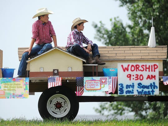 Cole Benning, 13, left, and his brother Carter Benning, both of Lennox, S.D., sit on the Turner County First Presbyterian Church float before the 4th of July Parade on Saturday, July 4, 2015, in Lennox, S.D.