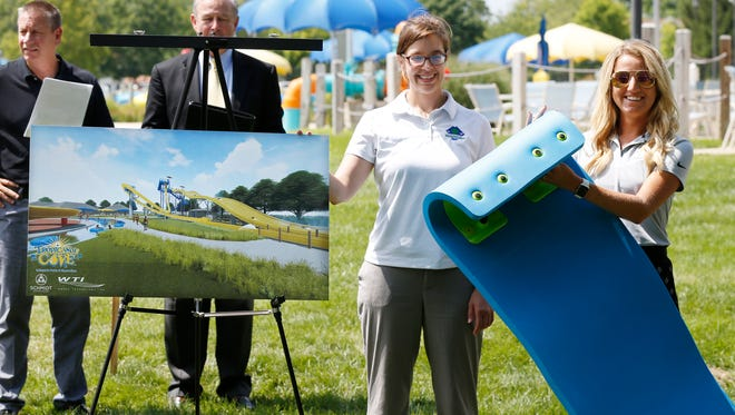 Arielle McKee, left, and Sarah Roswarski of Lafayette parks department display an artist rendering and a mat  as officials announce the construction of a Mat Racer Slide Monday, July 16, 2018, at Tropicanoe Cove. The Mat Racer Slide will open next May, the 20th anniversary of Tropicanoe Cove. The slide will be 44 feet high and feature six lanes. Mayor Tony Roswarski said the project will cost $2.7 million dollars.