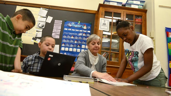 Nicolet Elementary School principal Becky Swanson works with students, from left, Juan Madrigal, Antwan Hollis, and Rahuina Smith in January.