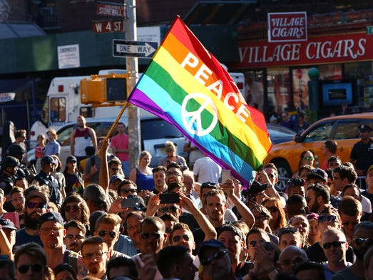 People gather outside of the Stonewall Inn to hold
