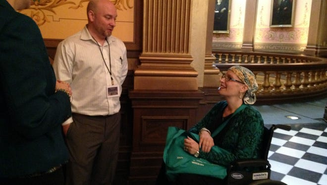In this May 17, 2016 photo, Ovarian cancer patient Amy Harvey, right, visits the Capitol to advocate for oral chemotherapy parity legislation in Lansing, Mich. Cancer patients and survivors are lobbying lawmakers to make Michigan the latest in a long line of states to require equal insurance coverage of chemotherapy regardless of whether the drugs are given by needle or taken orally.  (AP Photo/David Eggert)