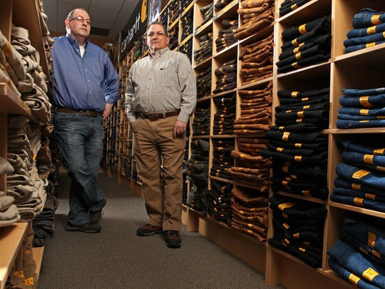Frank, right, and David Marcovis stand in the overflowing jeans section at G&L Clothing in Des Moines. The retailer is celebrating 100 years in business this week.
