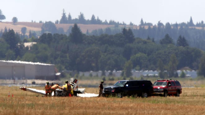 A heat haze blurs the view of members of the Salem Fire Department who responded to a fatal plane crash north of the runway on the Salem airport grounds on Saturday, July 4, 2015. The NTSB will be investigating the plane crash.