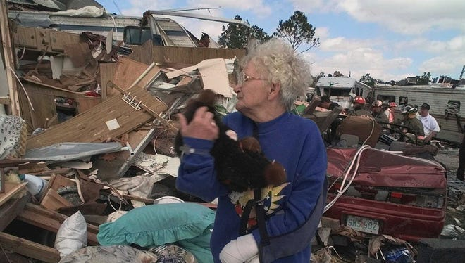 Betty Vorreiter clutches a stuffed animal that was recovered from her destroyed home in Kissimmee, Fla., in February 1998, where a tornado hit, killing dozens.