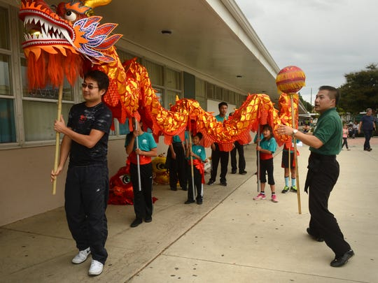 Eddy Hsu, left, works the head of the dragon as Si Fu Eric Kong, right, directs the Oct. 29 rehearsal for Saturday's Chinese Cultural Expo.