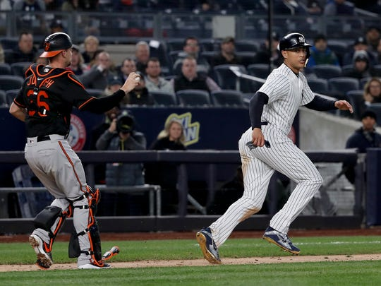New York Yankees' Giancarlo Stanton, right, moves away from Baltimore Orioles catcher Caleb Joseph (36) in a rundown on ball hit by New York Yankees' Neil Walker during the sixth inning of a baseball game, Friday, April 6, 2018, in New York. Stanton was out on the play.