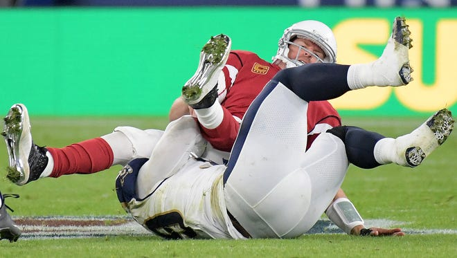 Arizona Cardinals quarterback Carson Palmer is sacked by Los Angeles Rams defensive end Aaron Donald in the second quarter during an NFL International Series game at Twickenham Stadium in London. Palmer broke his arm on the play.