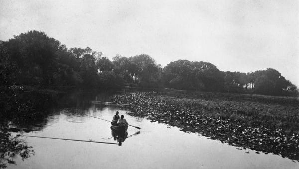 This image shows a two people fishing on the Caloosahatchee early in the 20th century.