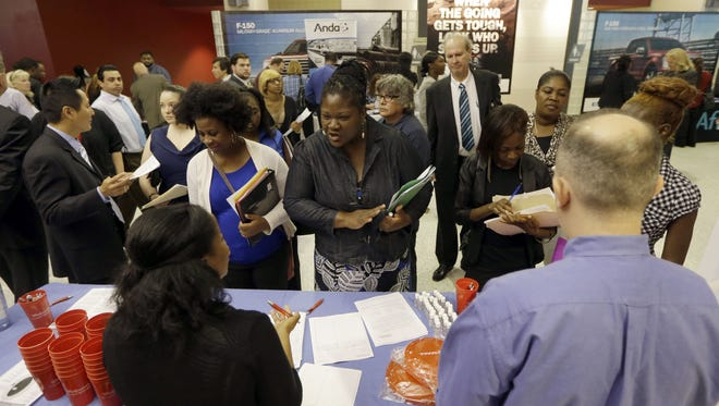 In this photo taken Wednesday, June 10, 2015, job seekers attend a job fair in Sunrise, Fla.