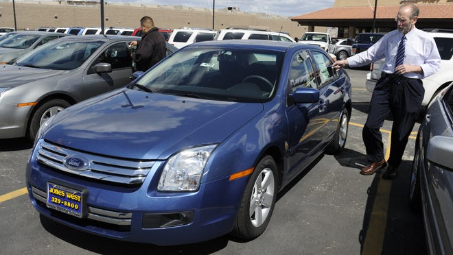 A sales manager at Jones West Ford, explains the features of a 2009 Ford Fusion on April 2, 2009.