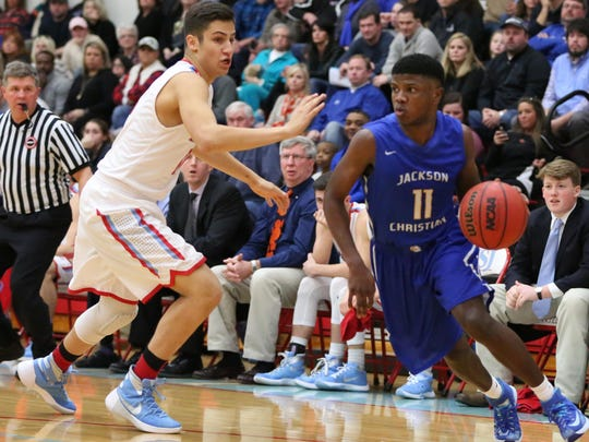 Jackson Christian's Josh Cole dribbles around USJ's Amir Kaveh on Saturday night.