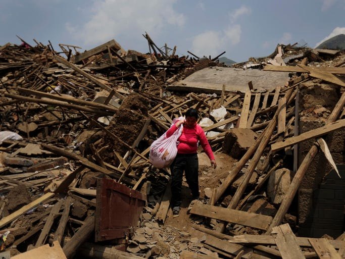 A woman carries her salvaged goods through earthquake-destroyed homes in Longtoushan, China, on Aug. 6.