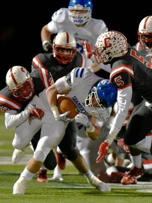 Catholic Central's Cam Ryan is brought down by a crowd of Chiefs.