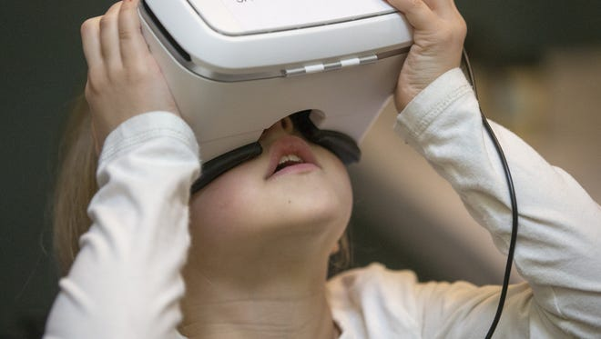 A girl looks through a virtual reality depiction of the view from the International Space Station, at a program at Conner Prairie focused on science, technology, engineering and math.