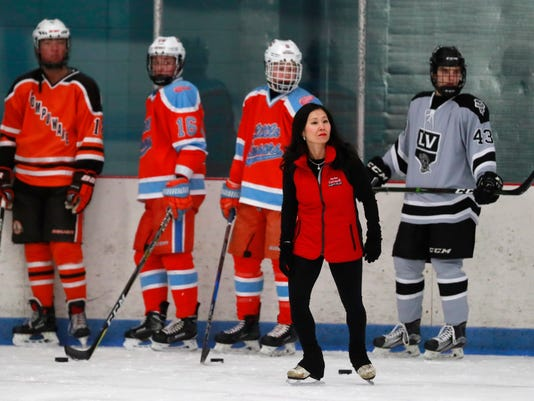 In this Wednesday, Feb. 7, 2018, photo from, skating coach Kim Muir skates next to her hockey clients at the Suburban Ice Arena in Farmington Hills, Mich. Muir, a renowned skating coach is returning to South Korea to cheer for clients playing hockey for the U.S. at the Olympics and to return to the site of her orphanage. As a 6-month-old girl, she was left next to a trash can on the streets of Seoul in the winter of 1974. (AP Photo/Carlos Osorio)