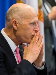 Florida Gov. Rick Scott listens during a statewide