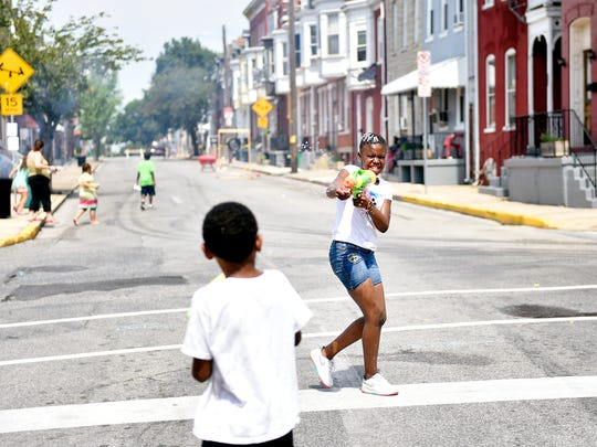 Aj Dickerson, 10, plays with a water gun Saturday during Crispus Attucks' 85th anniversary block party on South Duke Street. The association is hosting an event each month in 2016 to celebrate its anniversary as a nonprofit providing community development, education services and more.