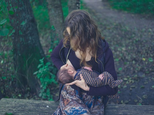 Mother breastfeeding baby in forest