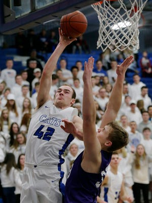 Oshkosh West's Derek Kroll goes up for a shot over Eau Claire Memorial's Cormac Sampson.