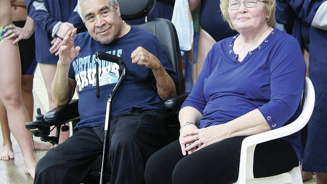 Shown with his lovely wife Brenda of nearly 50 years, Ram Gonzalez acknowledges the appreciation of the Bartlesville High School swim team, and the many spectators in attendance, during a ceremony on Nov. 1, 2018 to recognize him. During a home football game last fall, Bartlesville High also honored Gonzalez as part of its Hometown Heroes program. The beloved former educator and coach passed away last Friday, at age 78, in Bartlesville. Mike Tupa/Examiner-Enterprise
