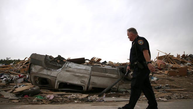 A police officer walks past an overturned car near a home that was destroyed by a tornado on April 29, 2014, in Vilonia, Ark.
