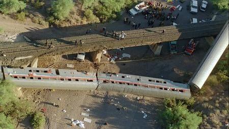 Three cars of the Amtrak Sunset Limited passenger train lie in a dry stream bed after the train derailed about 70 miles southwest of Phoenix Oct. 9, 1995.  One person was killed and more than 100 were reported injured in the derailment.