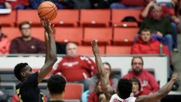 Oregon forward Chris Boucher, left, shoots while defended by Washington State guard Ike Iroegbu (2) during the first half of an NCAA college basketball game in Pullman, Wash., Saturday, Jan. 7, 2017. (AP Photo/Young Kwak)