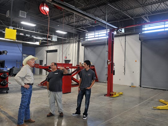Dan Shores, left, an industry advisor, talks with instructor Larry Krugle and former Automotive Technology student Luis Gonzalez at the new Career Education Center Tuesday.