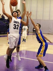 Mescalero's Cullen Orozco (32) tries to grab an offensive rebound Monday night.