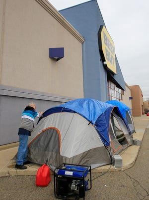 Edward Regec of Akron, Ohio, helps set up a tent belonging to his son, Tony Avitar, outside the Cuyahoga Falls, Ohio, Best Buy store on  Nov. 19, 2013.  The father and son hope to find good deals on televisions and laptops.