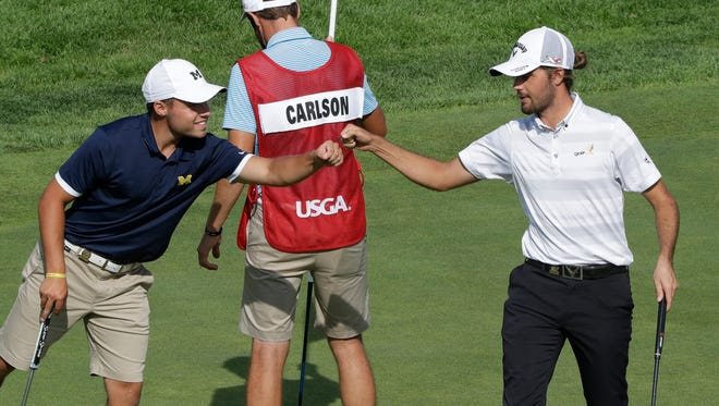 Nick Carlson, left, fist bumps Curtis Luck of Australia after their play on the 11th hole during a semi-final round of the U.S. Amateur golf tournament Saturday at Oakland Hills Country Club.