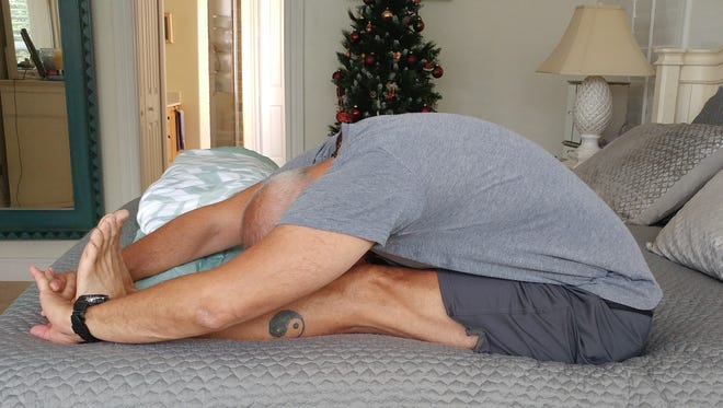 Gary Granza, who had knee replacement surgery nine month ago,  demonstrates forward fold.