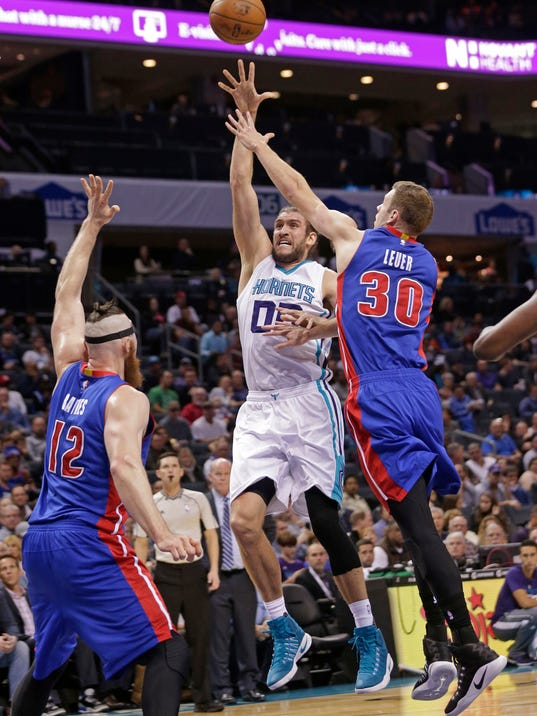 Charlotte Hornets' Spencer Hawes (00) shoots over Detroit Pistons' Jon Leuer (30) and Aron Baynes (12) during the first half of an NBA basketball game in Charlotte, N.C., Tuesday, Nov. 29, 2016. (AP Photo/Chuck Burton)