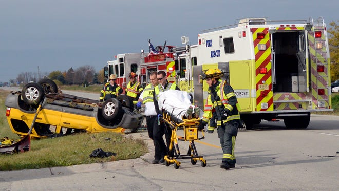 Officials use a stretcher to transport a crash victim to an awaiting ambulance at the corner of W. College Avenue and N. McCarthy Road Thursday, Oct. 23, 2014, in Grand Chute.