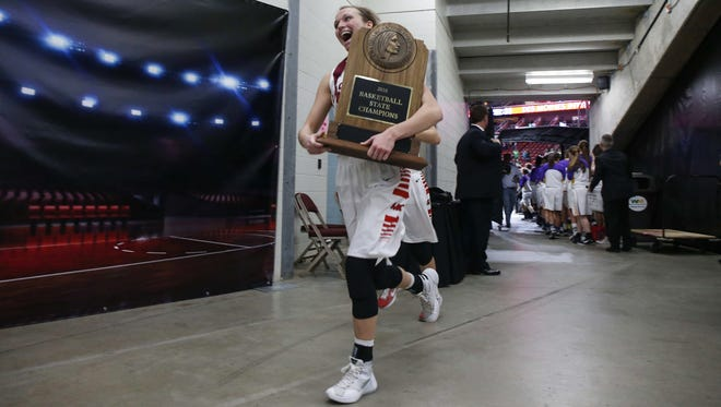 Mason City senior Makenzie Meyer runs down the hallway carrying the Iowa Class 4A state championship trophy after the Mohawks beat Pella at Wells Fargo Arena in Des Moines on Saturday, March 5, 2016.