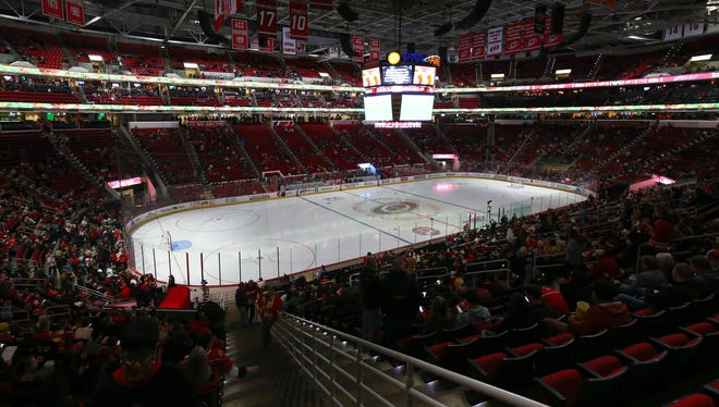 The Hurricanes and Red Wings fans wait for the game to start because of a delay to mechanical problems with the ice at PNC Arena on Monday. The game was eventually canceled.