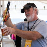 Volunteer Mark Mayer pours a golden ale draft beer from the SanTan Brewing Company at the Great American BBQ and Beer Festival at Chandler Park Saturday March 21, 2015 in Chandler, Arizona.