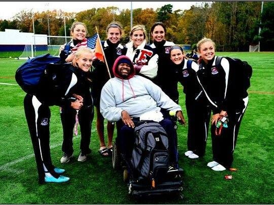 Bruce Jackson (front, center) is surrounded by members of the Eastern Regional High School girls' soccer team following  a game this past season.