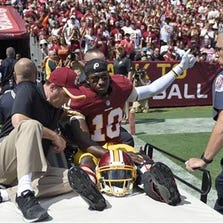 Washington Redskins quarterback Robert Griffin III (10) leaves the game on a cart after injuring his left ankle during the first half of an NFL football game against the Jacksonville Jaguars on Sunday, Sept. 14, 2014, in Landover, Md.