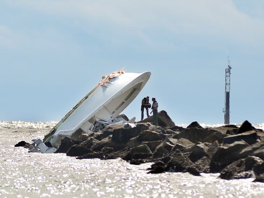 "In this Sept. 25, 2016, file photo, investigators inspect an overturned boat as it rests on a jetty after a crash off Miami Beach, Fla. Miami Marlins pitcher Jose Fernandez was the ""probable"" operator of a speeding boat that crashed into a Miami Beach jetty on Sept. 25, 2016, killing the star baseball star and two other men, according to a report issued Thursday, March 16, 2017, by the Florida Fish and Wildlife Conservation Commission, which investigated the accident."