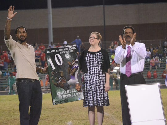 Former Peabody receiver Emmanuel Arceneaux (left) waves to the crowd as he holds up a framed poster that was presented to him by Principal Jamie Henagan and athletics director Charles Smith (right) at halftime of Friday night's game. Arceneaux, a standout receiver for the CFL's British Columbia Lions, was one of two former Warhorses to have his number retired Friday night.