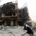 "Iraqi women walk past a damaged building at the site of a suicide car bombing claimed by the Islamic State group on July 3, 2016, in Baghdad's central Karrada district. The blast, which ripped through a street in the Karrada area where many people go to shop ahead of the holiday marking the end of the Muslim fasting month of Ramadan, killed at least 75 people and also wounded more than 130 people, security and medical officials said. The Islamic State group issued a statement claiming the suicide car bombing, saying it was carried out by an Iraqi as part of the group's ""ongoing security operations."""