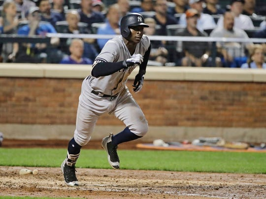 Yankees' Didi Gregorius runs toward first base while