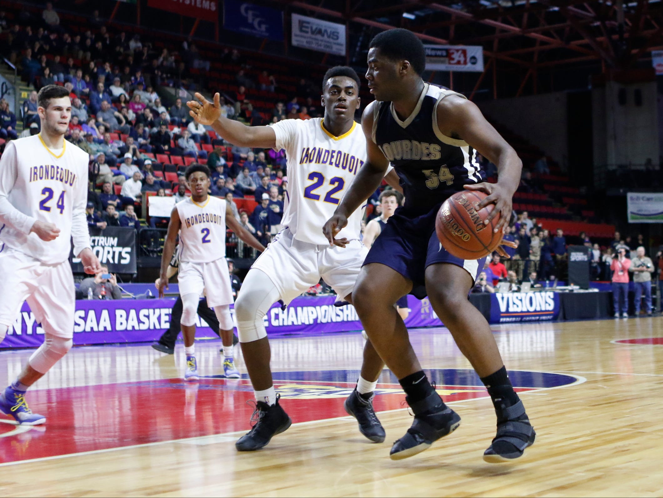 Lourdes' James Anozie looks to attack the basket during the Class A state final against Irondequoit.