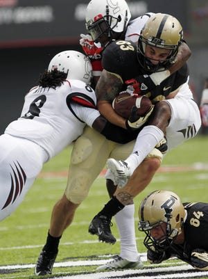 Purdue's Bj.Knauf is tackled by  Cincinnati defenders Adrian Witty and Trenier Orr. (Tony Tribble for the Enquirer)