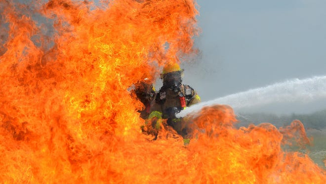 Firefighters work to put out flames during a training exercise at Capital Region International Airport.