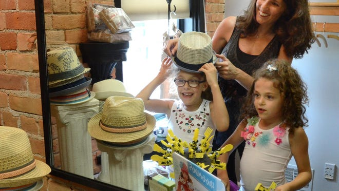 Ambrosia Vae owner Amber Witt gets some modeling help from her daughters Ava, 8, and Harley, 7, right, at her downtown South Lyon children's boutique. Ambrosia Vae is located at 105 N. Lafayette.