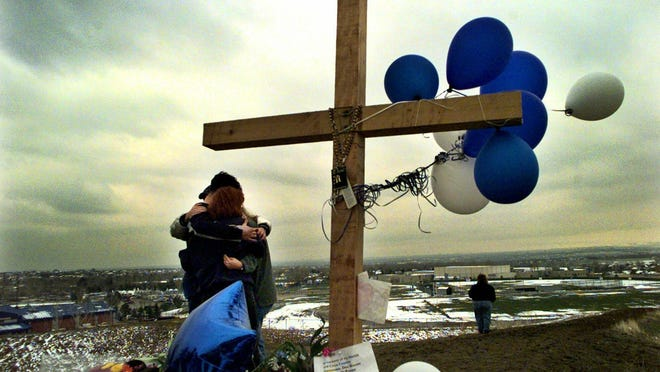 Students embrace in 1999 at a makeshift memorial for their slain classmates at Columbine High School on a hilltop overlooking the school in Littleton, Colo. Twelve students and one teacher were killed in a murderous rampage at the school on April 20, 1999, by two students who killed themselves in the aftermath.